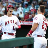 Shohei Ohtani is greeted by Mike Trout as he returns to the dugout following his home run against the Mariners on Saturday in Anaheim, California. | KYODO