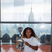 Naomi Osaka of Japan poses with her championship trophy at the Rock Observation Deck at the Rockefeller Center in New York on Sunday, the morning after defeating Serena Williams of the United States, winning the 2018 U.S. Open Women's Singles Finals. | AFP-JIJI