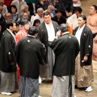 The five judges, also known as shinpan, meet on the dohyo Thursday at the Autumn Grand Sumo Tournament in Tokyo. | NIKKAN SPORTS