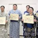 New wrestlers display their certificates of completion after graduating from the sumo school's orientation class, which is administered regularly at Ryogoku Kokugikan.