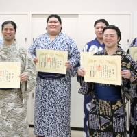 New wrestlers display their certificates of completion after graduating from the sumo school's orientation class, which is administered regularly at Ryogoku Kokugikan. | KYODO