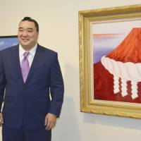 Former yokozuna Harumafuji poses with one of his paintings on the first day of an exhibition of his work at a gallery in Tokyo's Ginza district on Wednesday. | KYODO