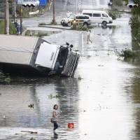 A truck lies on its side in the aftermath of powerful Typhoon Jebi in the Suminoe Ward of Osaka on Tuesday evening.    KYODO
