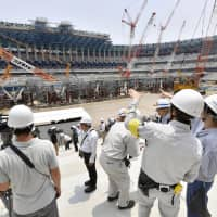 Media representatives are given a tour of the new National Stadium under construction in central Tokyo on July 18. | KYODO