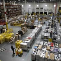 Workers prepare to move products at an Amazon fulfillment center in Baltimore last year. Amazon's announcement Tuesday that it will raise its minimum wage to $15 an hour will intensify the pressure on other companies to also lift their pay levels, particularly retailers and warehouse operators that are looking to staff up for the holidays. | AP