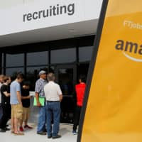 Job seekers line up to apply during 'Amazon Jobs Day,' a job fair at the Amazon.com Fulfillment Center in Fall River, Massachusetts, in 2017. | REUTERS