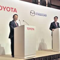 Toyota Motor Corp. President Akio Toyoda (left) and Mazda Motor Corp. head Masamichi Kogai hold a news conference in Tokyo to announce a capital tie-up on Aug. 4, 2017. | YOSHIAKI MIURA
