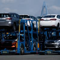 Toyota Motor Corp. vehicles are seen on a car transporter at Nagoya port on July 31. The government and the ruling parties are considering freezing a new duty on vehicles after the planned new sales tax comes into force next October. | BLOOMBERG