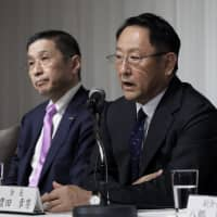 Akio Toyoda (right), president of Toyota Motor Corp. and chairman of Japan Automobile Manufacturers Association Inc., speaks during a news conference in Tokyo in May. | BLOOMBERG