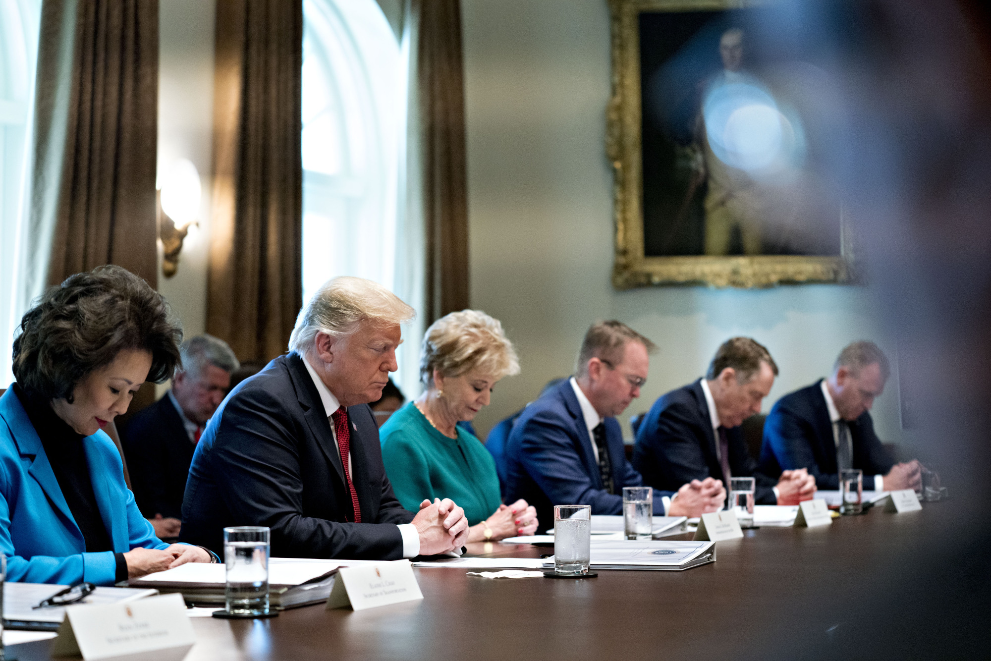 Elaine Chao, U.S. secretary of transportation (from left), U.S. President Donald Trump, Linda McMahon, administrator of the Small Business Administration (SBA), Mick Mulvaney, director of the Office of Management and Budget (OMB), and Robert Lighthizer, U.S. trade representative, listen to a prayer by Ben Carson, secretary of Housing and Urban Development (HUD) (not pictured) during a meeting in the Cabinet Room of the White House in Washington on Wednesday. | BLOOMBERG