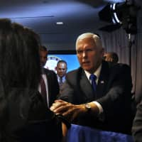 Vice President Mike Pence greets people after speaking Thursday at the Hudson Institute in Washington. Pence said China was using its power in 'more proactive and coercive ways to interfere in the domestic policies and politics of the United States.' | AP