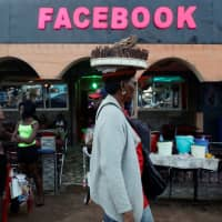 A street vendor walks past a bar called 'Facebook' in Yaounde Tuesday. | REUTERS