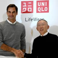Swiss tennis player Roger Federer shakes hands with Tadashi Yanai, president of Uniqlo parent Fast Retailing Co., during a photo session at a news conference at the Fast Retailing headquarters in Tokyo on Tuesday. | AFP-JIJI