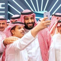 A handout picture provided by the Saudi Royal Palace on Tuesday shows Saudi Crown Prince Mohammed bin Salman (center) posing for a selfie with an unidentified man near Saudi billionaire Prince Al-Walid bin Talal (right) during the Future Investment Initiative FII conference in Riyadh. Saudi Arabia is hosting the key investment summit overshadowed by the killing of critic Jamal Khashoggi that has prompted a wave of policymakers and corporate giants to withdraw. | BANDAR AL-JALOUD / SAUDI ROYAL PALACE / VIA AFP-JIJI