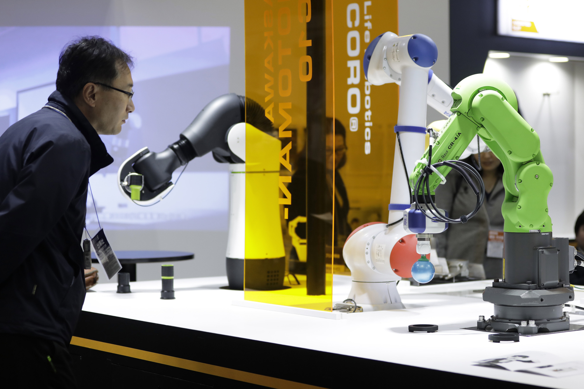 An attendee looks at a Fanuc Corp. CR-4iA industrial robot (right) at the RoboDEX exhibition in Tokyo on Jan. 18. | BLOOMBERG