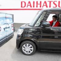 Yorie Miho tries out the automatic emergency braking system in a Daihatsu minicar at a minicar dealership in Yamato, Kanagawa Prefecture. | REUTERS