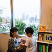 Yukie Watabe spends time with her son at her home in Tokyo on Sept. 10. | BLOOMBERG