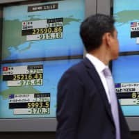 A man walks past an electronic stock board showing the Nikkei 225 average and other countries' indices at a securities firm in Tokyo on Thursday. Asian markets were broadly lower the same day after Wall Street slumped following a heavy sell-off of technology and internet stocks. | AP