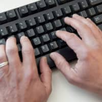 A man types on a computer keyboard in Washington in 2016. An elite group of North Korean hackers has been identified as the source of a wave of cyberattacks on global banks that has netted 'hundreds of millions' of dollars, security researchers said. A report by the cybersecurity firm FireEye said the newly identified group dubbed APT38 is distinct from but linked to other North Korean hacking operations, and has the mission of raising funds for the isolated Pyongyang regime. | AFP-JIJI