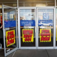 A woman walks out the door past signs advertising store closing at a Sears istore n New Hyde Park, New York, Wednesday. | REUTERS