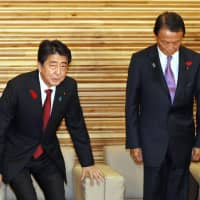 Prime Minister Shinzo Abe and Finance Minister Taro Aso attend an extraordinary Cabinet meeting Monday. Abe formally announced that the government will raise the consumption tax to 10 percent in October 2019. | KYODO