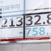 A passerby walks past a stock board in Tokyo's Nihonbashi district showing the Nikkei average index falling on the Tokyo Stock Exchange on Thursday morning. The day's closing price was at a seven-month low of 21,268.73. | KYODO