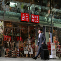 A pedestrian walks past Fast Retailing Co.'s flagship Uniqlo store in Osaka in April. Strong sales supported the group's net profit, which rose to a record high in the year through August. | BLOOMBERG