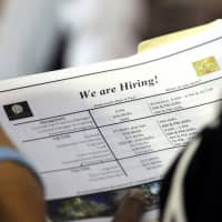A job applicant looks at job listings for the Riverside Hotel at a job fair hosted by Job News South Florida, in Sunrise, Florida, in June. | AP
