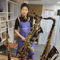 Lacquered up: Yurie Akaiwa shows off her urushi-lacquered saxophones in a shop in Toyama Prefecture last month. | KYODO
