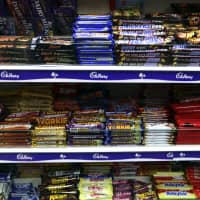 Chocolate confectionary bars are displayed for sale at a store in London in 2013. Chinese internet giant Alibaba has helped Mars Inc. create a new Snickers candy bar that incorporates Sichuan peppercorn, based on its vast trove of shoppers' data. | BLOOMBERG