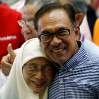 Anwar Ibrahim celebrates his by-election victory with his wife, Wan Azizah, on Saturday in Port Dickson, Malaysia. | REUTERS