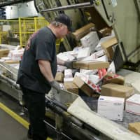 Steve Robino arranges packages on a conveyor belt at the main post office in Omaha, Nebraska, last December. The shipment of several pipe bombs to CNN and several prominent Democrats raises fresh questions about mail safety and what measures the U.S. Postal Service and private delivery services take to prevent explosives and other illegal substances from entering into the mail. | AP