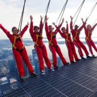 Six new Canadians pose while harnessed to the top of the CN Tower, before taking their oath of citizenship on the 'Edgewalk' 365 meters (1,668 feet) above Toronto Tuesday. | CN TOWER / HANDOUT / VIA REUTERS