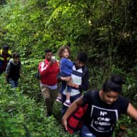 Honduran migrants hike in the forest after crossing the Lempa river, on the border between Honduras and Guatemala, to join a caravan trying to reach the U.S., in Guatemala Thursday. | REUTERS