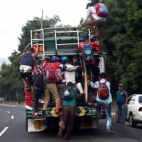 Honduran migrants, part of a caravan trying to reach the U.S., climb on a bus during a new leg of their travel, in Guatemala City Thursday. | REUTERS