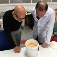 Lancaster University researchers Mohamed Saafi and Hasan Hasan look into a bucket containing carrot mixture to be added to concrete in their laboratory in Lancaster, England, on Oct. 2. | REUTERS