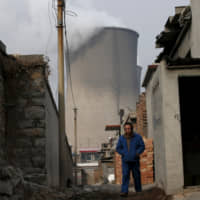 A man makes his through a village which is next to cooling towers of a coal-fired power plant in Shijiazhuang, in China's Hebei province, in 2015. | REUTERS