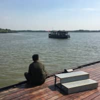 A worker waits for a tour boat to dock at an artificial lake built in a former coal mining district of Xuzhou, Jiangsu province, in September. | REUTERS