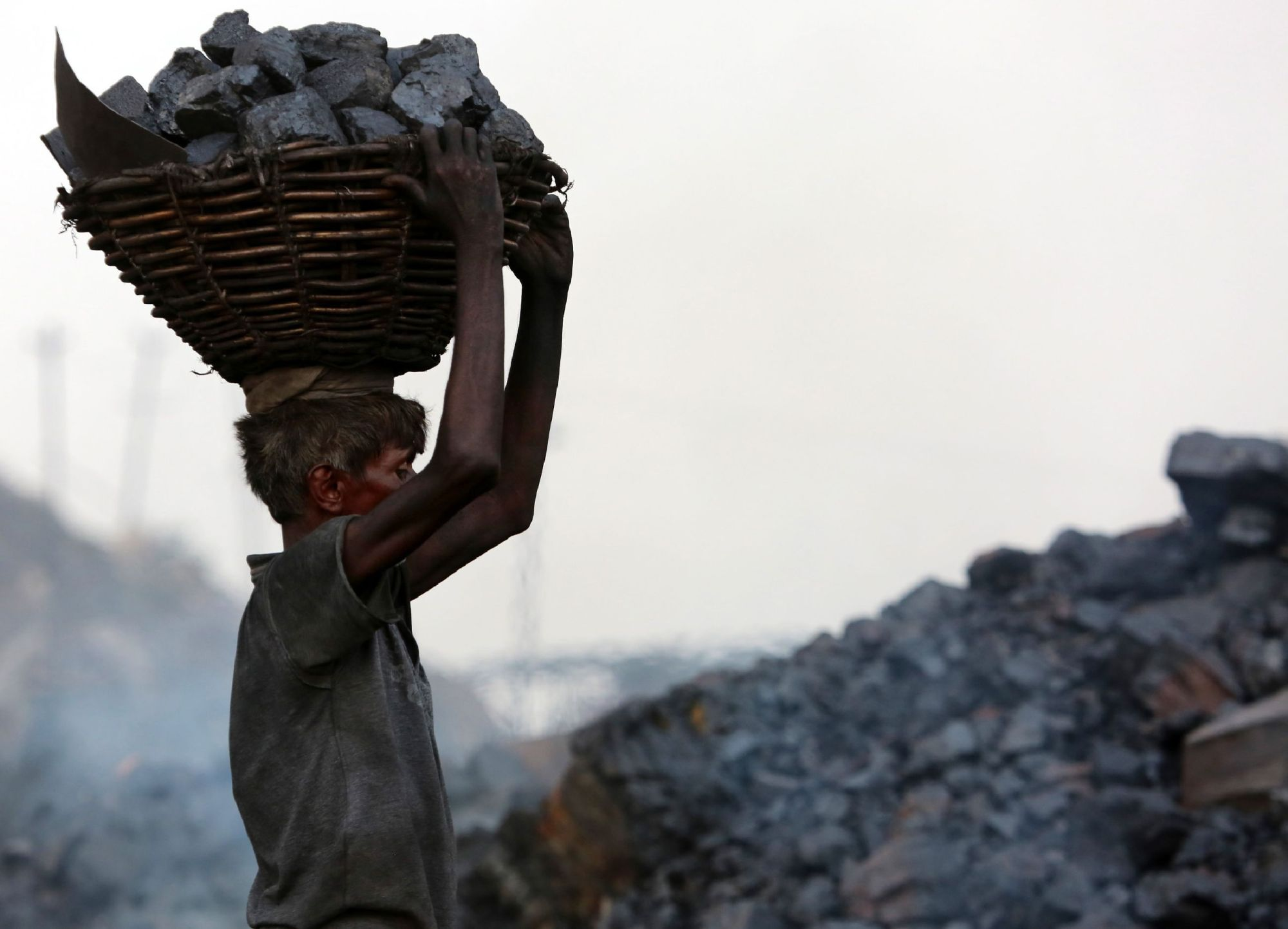 An coal scavenger carries a basket of coal collected at a mine in the district of Dhanbad, in India's Jharkhand state, at the end of June last year. | AFP-JIJI