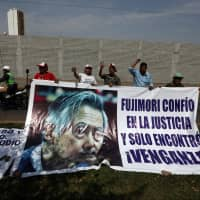 Supporters of former President Alberto Fujimori hold a banner with a picture of him outside the Centenario hospital where he is hospitalized, after a judge annulled a presidential pardon and ordered his immediate capture and return to prison, in Lima Thursday. The banner reads: 'Fujimori trusted in justice and found only revenge.' | REUTERS