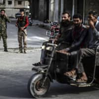 Fighters of the Syrian opposition stand near a checkpoint in northwestern city of Idlib, Syria, late Saturday.   UGUR CAN / DHA / VIA AP