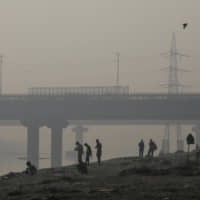 People are seen silhouetted against the morning light on the banks of the Yamuna River in New Delhi on Thursday. As energy-hungry India seeks to fuel continued economic growth, millions of people are being robbed of their homes by companies building power plants on their land or mining the coal below it, activists and villagers say. | REUTERS