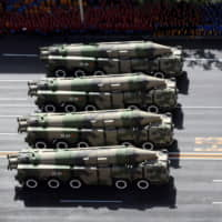 Chinese military vehicles carrying DF-21C medium-range ballistic missiles parade through Beijing's Tiananmen Square during a military parade marking the 60th anniversary of the founding of the Peoples Republic of China in October 2009. | IMAGINECHINA / VIA AP