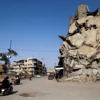 Syrians ride their motorcycles past a damaged building in the Syrian city of Raqqa on Thursday. A year after a U.S.-backed alliance of Syrian fighters drove the Islamic State group from the northern city of Raqa, traumatized civilians still live in fear of near-daily bombings. | AFP-JIJI