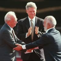 Then-U.S. President Bill Clinton applauds as Jordan's King Hussein Ibn Talal (right) and Israeli Premier Yitzhak Rabin shake hands during the Israeli-Jordanian Peace Treaty signing ceremony at the Araba Israeli-Jordanian border in 1994.  Jordan's King Abdullah II announced Sunday that his country has notified Israel of its intention to reclaim territories leased under the 1994 peace deal, the official Petra news agency reported. | SVEN NACKSTRAND / VIA AFP-JIJI
