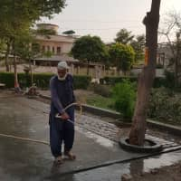 A gardener washes a walkway in Lahore's Johar Town area on Tuesday. A petition being heard before the Lahore High Court seeks to stop the city from using 30,500 liters of water each day to wash its streets. | THOMSON REUTERS FOUNDATION / WAQAR MUSTAFA