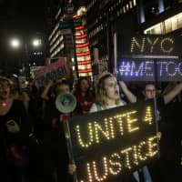Demonstrators hold signs during a protest and march against the U.S. Supreme Court nominee Brett Kavanaugh in New York City Monday. | REUTERS
