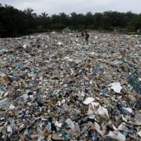 Plastic waste lies outside an illegal recycling factory in Jenjarom, Malaysia, on Oct. 14. | REUTERS