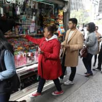 New Yorkers line up to buy Mega Millions tickets at a newsstand in midtown Manhattan on Friday. | REUTERS