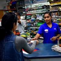 Twinkle Patel sells a Powerball ticket Wednesday at the KC Mart in Simpsonville, South Carolina, where the near-record Mega Millions ticket had been sold. | REUTERS
